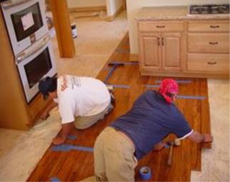 Lay Subsequent Rows Of Flooring By Applying Glue To Side And End Joints And  Fitting Planks Together With Tapping Block.